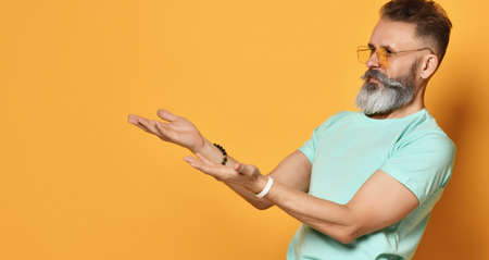 bright elderly man with a beard stretches out two hands in surprise in surprise that you are suggesting I do not understand you Stock Photo
