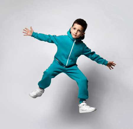 Boy in warm tracksuit jumping up isolated studio shot Foto de archivo