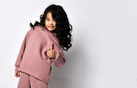 Full portrait of happy smiling asian girl, wearing modern sweatshirts and pants