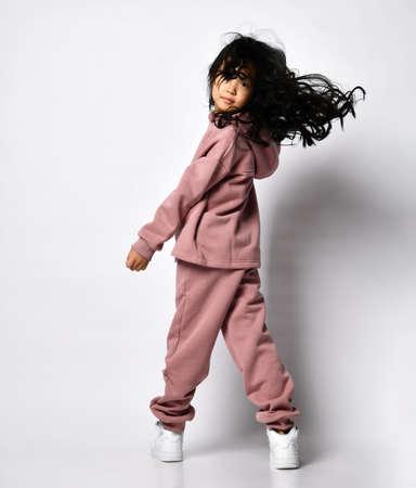 Full portrait of happy smiling asian girl, wearing modern sweatshirts and pants Foto de archivo
