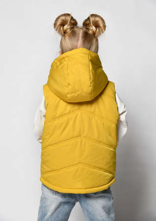 Girl in casual yellow outwear sleeveless vest with hood back view studio shot 版權商用圖片