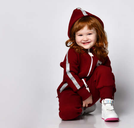 Little preschooler girl wearing warm tracksuit sitting on studio floor