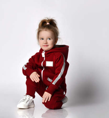 Little preschooler girl wearing warm tracksuit sitting over studio copy space