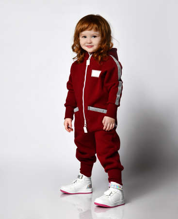 red-haired preschooler girl wearing warm tracksuit studio portrait 版權商用圖片