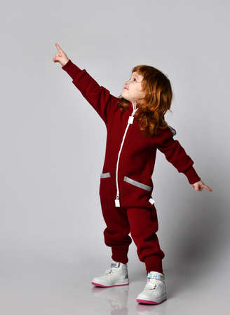 Joyful little red-haired toddler girl in warm sports overalls side view portrait
