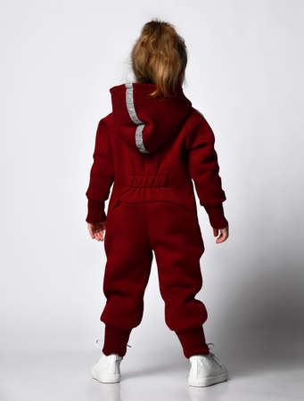 Rear view of little preschooler girl wearing warm tracksuit studio portrait