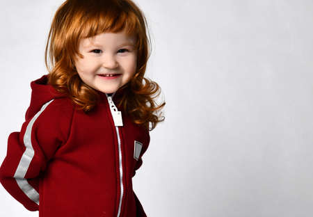 Cheerful sly smiling redhead girl in a burgundy hoodie jumpsuit looking at us on a gray background