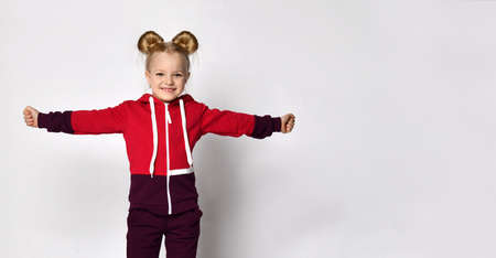 little blonde curly-haired beautiful girl in a red burgundy tracksuit stands with her arms spread wide like wings, playing an airplane or a bird on a gray wall background. 版權商用圖片