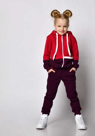 little blonde curly-haired beautiful girl in a red burgundy tracksuit and white sneakers stands with her hands in her pockets and is shy. over gray wall background.