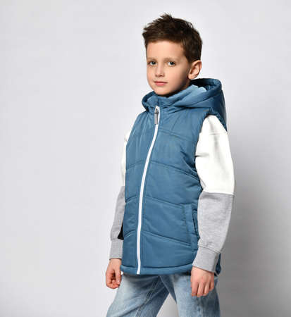 smiling teenager in a quilted or down jacket vest, ready to spend winter holidays and vacations in comfort and warmth, presenting the product, copy space