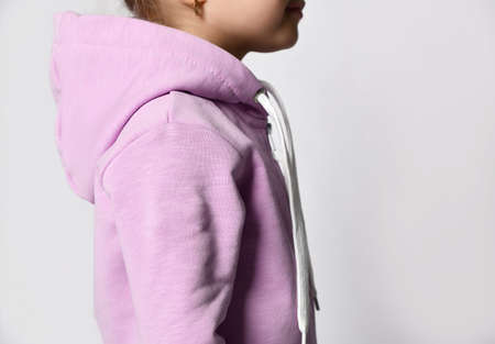 Child in sportive suit put on hood standing back cropped shot 版權商用圖片