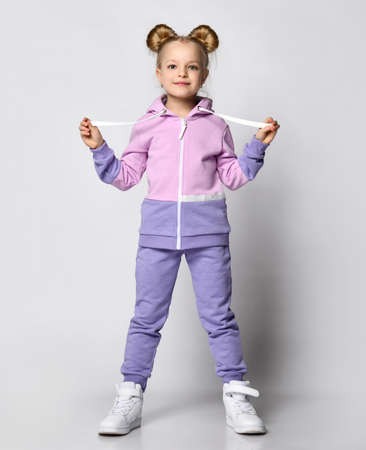 Happy little girl with a funny hairstyle posing in full growth in a cozy suit for sports and walking. Girl holding laces from the hood