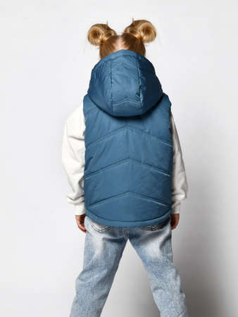 Girl in casual blue outwear sleeveless vest with hood back view studio shot