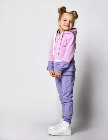 Girl in pink violet sportive suit posing for camera studio shot