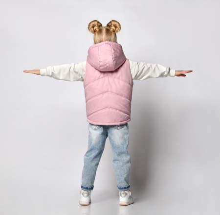 Girl in casual pink outwear sleeveless vest with hood back view studio shot 版權商用圖片