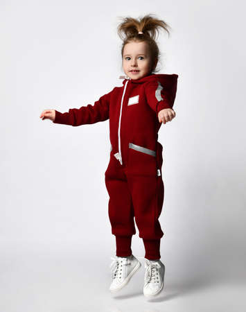 Little preschooler girl wearing warm tracksuit jumping over studio copy space