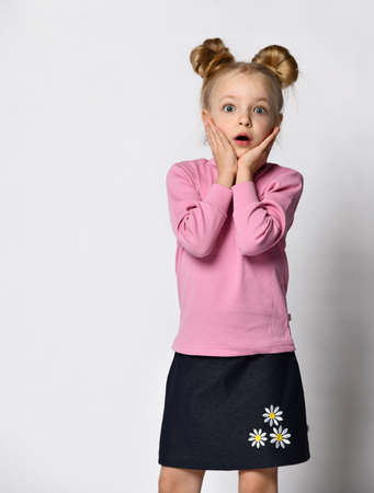 Shocked amazed little preteen girl in skirt and raglan studio shot