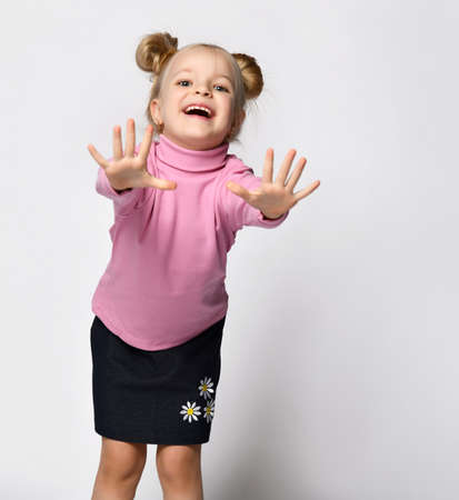 Little smiling preteen girl in skirt and raglan stretching hand to camera studio shot