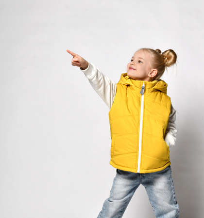 pretty smiling blonde girl in a yellow puffy vest is standing with her hand in her pocket and pointing with her other hand.