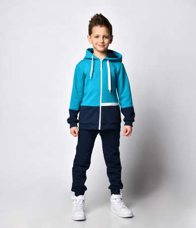 Boy in warm sportswear standing on studio