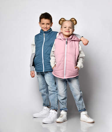 Pre-teen boy and little girl in casual outwear vest studio shot