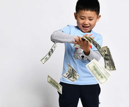 Cool little asian boy throwing money cash studio shot