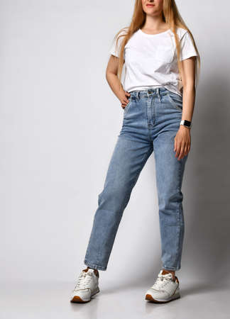 Unknown young skinny woman dressed in stylish blue jeans and white sneakers.