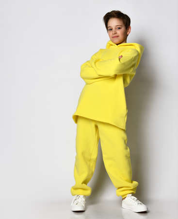 Full length portrait of a teenage boy dressed in a bright yellow sports suit.