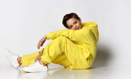 Stylish active guy in a bright yellow sports suit having fun on a white background.