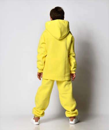 back view of a guy in a bright yellow tracksuit with a hood, on a light background Standard-Bild