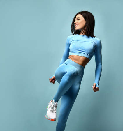 Slender beautiful female athlete with a perfect body in sportswear on a blue background. Standard-Bild