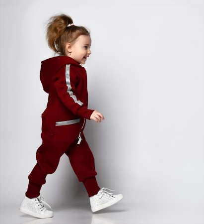 Little preschooler girl wearing warm tracksuit walking over studio copy space