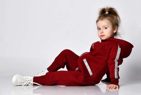 Cute little preschooler girl wearing warm tracksuit sitting looking at camera