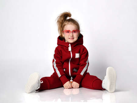 cute preschool girl sitting on the floor in a comfortable overalls Standard-Bild