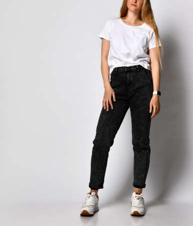 Studio shot of unrecognizable stylish young woman in black jeans and white t-shirt.
