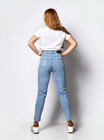 young skinny woman dressed in stylish blue jeans and white sneakers.
