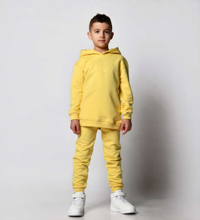 Stylish brunet boy child in a sports sweatshirt with a hood and pants stands with a hood over his head, hands in his pockets. Standard-Bild