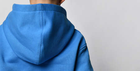 Close-up view from the back, focus on the hood of the boys blue sweater. Standard-Bild