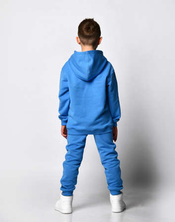 Full-length portrait of a boy with a stylish haircut in modern pastel shades of blue with a hood and trousers, standing with his back to camera over white white background.