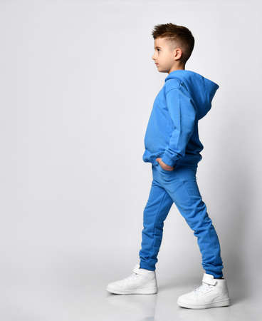 Full-length portrait of a boy with a stylish haircut in modern pastel shades of blue with a hood and trousers, standing sideways in front of the camera