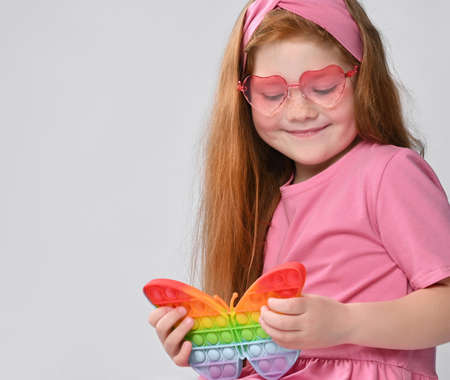 Smiling little red-haired girl child playing with  toy studio shot Standard-Bild