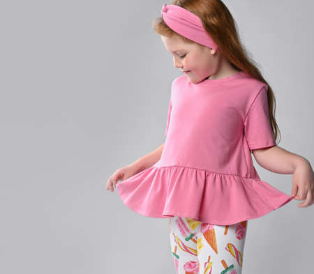 Pensive little red-haired girl child demonstrating summer fashion look Standard-Bild