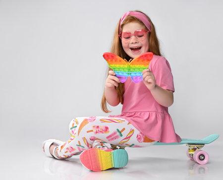 Happy surprised little red-haired girl child toy studio shot Standard-Bild