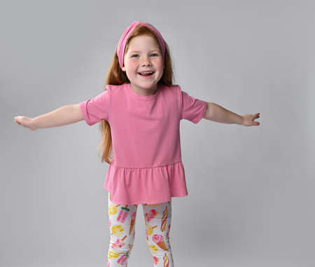 Happy little red-haired girl child widely spreading arms ready to hug Standard-Bild