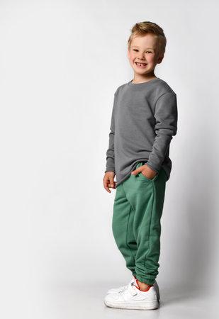 Funny giggling european little boy demonstrating sportswear in studio