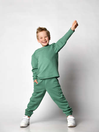 Cute little boy child with hand in pocket and one raised up dancing