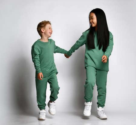 Portrait of smiling asian preteen girl hugging little laughing european boy Standard-Bild