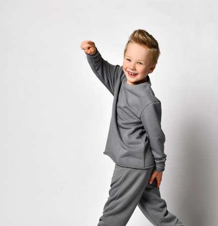 Little boy turning and pointing finger to camera studio shot Standard-Bild