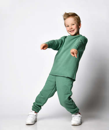 emotional portrait of Caucasian teenage boy in tracksuit. Surprised teenager looking at camera. Beautiful happy baby isolated on white background.