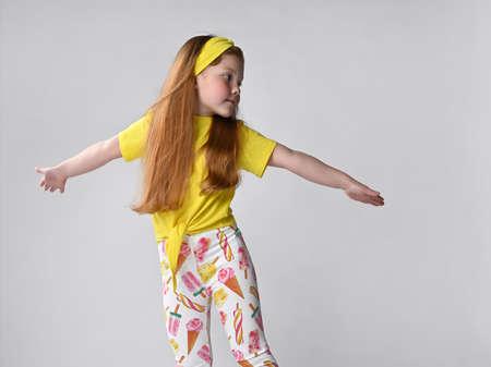 Studio shot of happy little red-haired girl child flying like plane